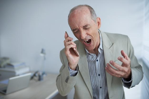 Empresário caucasiano careca com raiva, segurando o telefone móvel e gritando de raiva