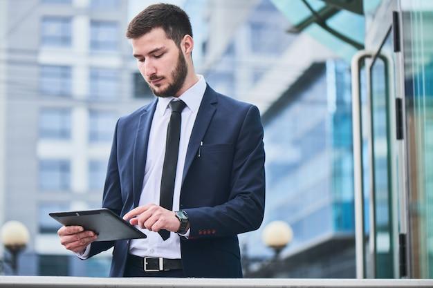 Empresário caucasiano com laptop em um fundo de um edifício de negócios