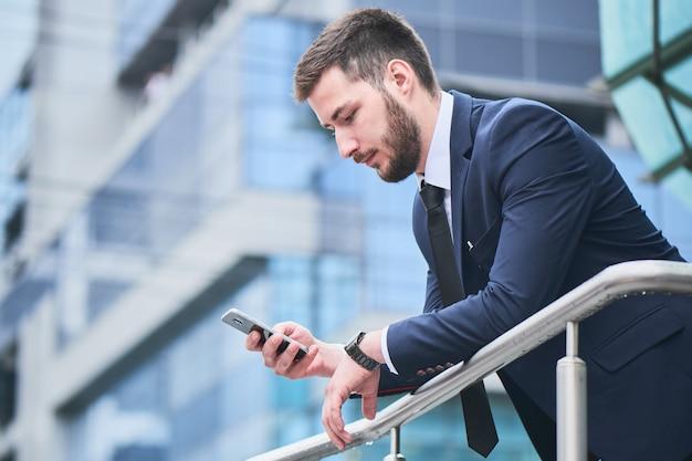 Empresário caucasiano fala pelo telefone móvel no contexto de um edifício comercial