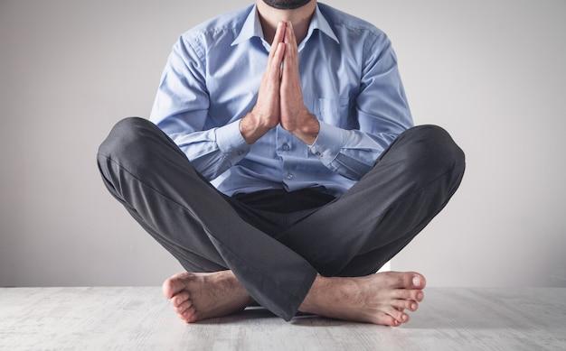 Empresário caucasiano meditando no escritório. posição de lótus. relaxar