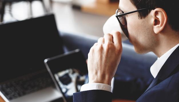 Empresário caucasiano ocupado com óculos está bebendo um café e usando um tablet e laptop