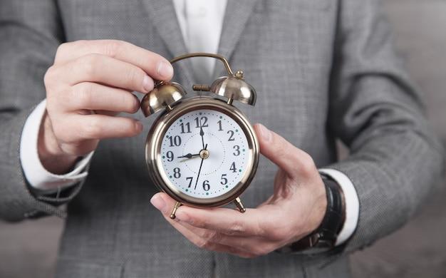 Empresário caucasiano segurando o relógio despertador.