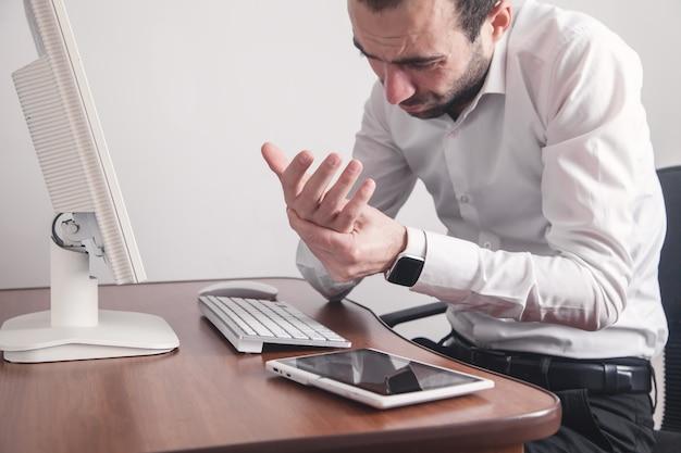 Empresário caucasiano, sofrendo de dor nas mãos no escritório.