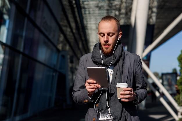 Empresário caucasiano usando computador tablet com fones de ouvido, andando perto do centro de negócios durante uma pausa para o almoço de trabalho.