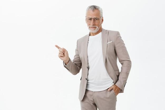 Empresário cético de terno e óculos apontando o dedo para a esquerda em dúvida