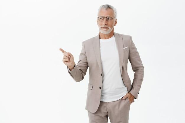 Empresário cético de terno e óculos apontando o dedo para a esquerda, pensativo