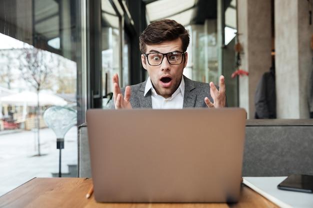 Empresário chocado em óculos, sentado junto à mesa no café, olhando para o computador portátil