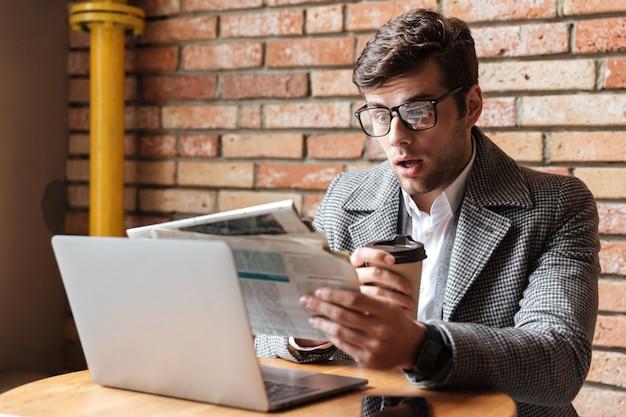 Empresário chocado em óculos, sentado junto à mesa