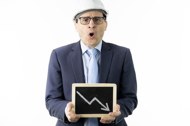 Empresário chocado mantém tablet com seta para baixo, citações de óleo em declínio