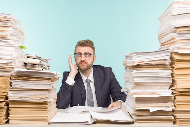Empresário chocado sentado à mesa com muitos papéis no escritório