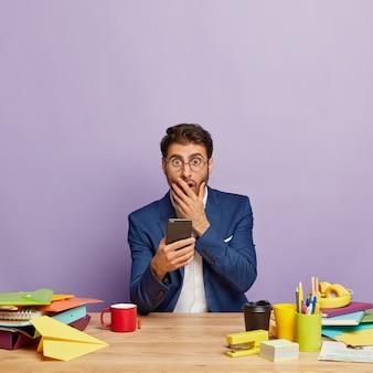 Empresário chocado sentado na mesa do escritório