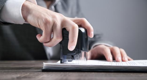 Empresário coloca um carimbo nos documentos no escritório.