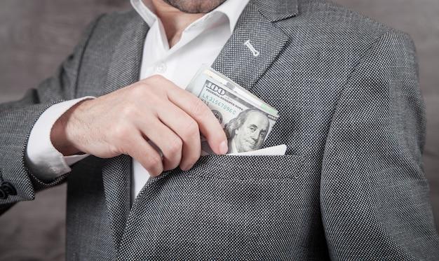 Empresário, colocando as notas de dólar no bolso.