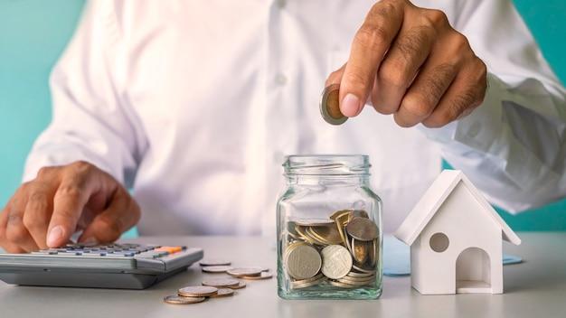 Empresário colocando dinheiro em uma garrafa de poupança e modelo de casa, conceito financeiro. crédito à habitação e empréstimos imobiliários residenciais