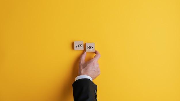 Empresário colocando dois blocos de madeira com palavras sim e não sobre fundo amarelo. com espaço de cópia.