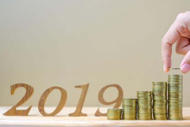 """Empresário colocando e dinheiro contábil com o número """"2019"""""""
