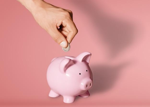 Empresário colocando moeda no cofrinho