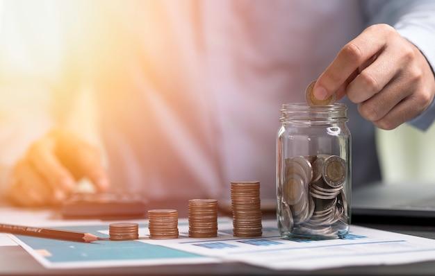 Empresário colocando moedas para salvar o frasco e usar a calculadora. economizando dinheiro para o conceito de investimento em contabilidade financeira.