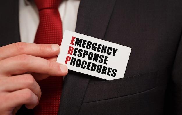 Empresário colocando no bolso um cartão com o texto erp procedimentos de resposta de emergência