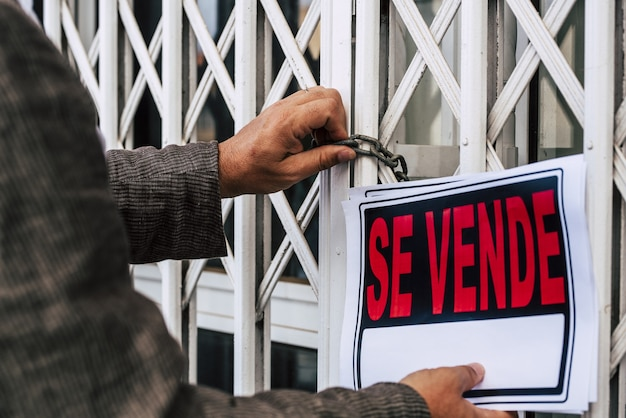 Empresário colocando para venda assinar em exposição na loja ou escritório trancado devido ao surto de pandemia de coronavírus. encerramento governamental de serviços não essenciais. vender devido à falência