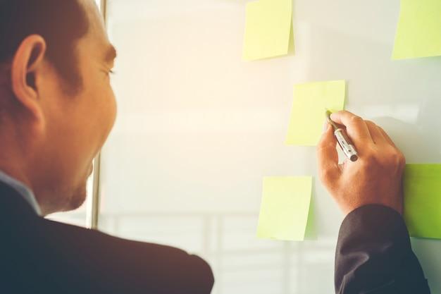 Empresário colocando suas idéias no planejamento post-it no novo projeto de negócios