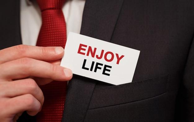 Empresário colocando um cartão com o texto aproveite a vida no bolso