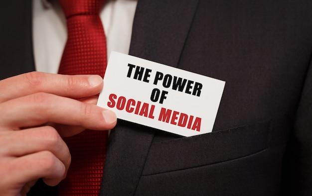Empresário colocando um cartão com o texto o poder da mídia social no bolso