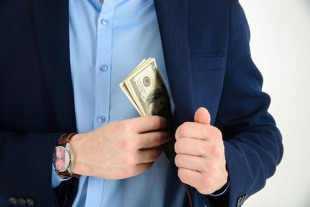Empresário colocar dinheiro no bolso do terno