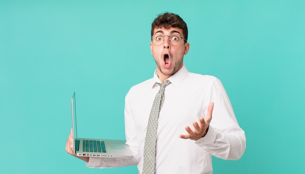 Empresário com a boca aberta no laptop e surpreso, chocado e surpreso com uma surpresa inacreditável