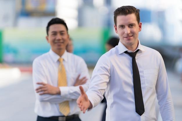 Empresário com a mão aberta pronta para um aperto de mão para selar um negócio em frente a um escritório de edifícios de escritórios modernos