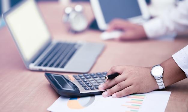 Empresário com a mão segurando a caneta, trabalhando na calculadora para calcular os dados de informações de negócios
