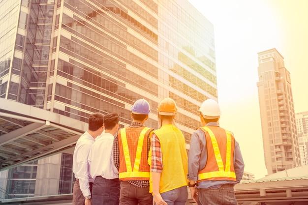 Empresário com acordo de reunião do grupo de engenheiros para construção e olhando em arranha-céus na cidade. tom de filtro de luz solar