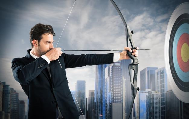 Empresário com arco e flecha mirando um alvo