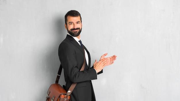 Empresário com barba aplaudindo após apresentação em uma conferência