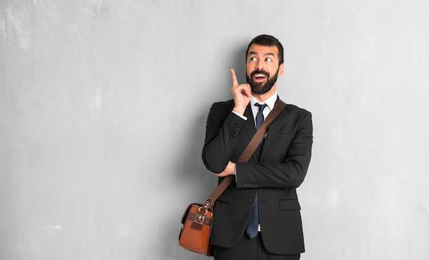 Empresário com barba em pé e pensando uma ideia apontando o dedo para cima