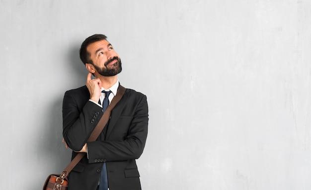 Empresário com barba em pé e pensando uma idéia enquanto coçando a cabeça