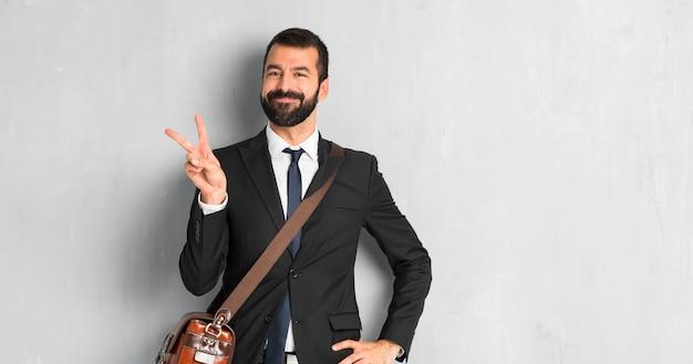 Empresário com barba sorrindo e mostrando sinal de vitória com uma cara alegre