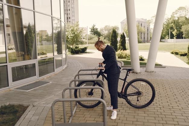 Empresário com bicicleta em uma cidade de verão