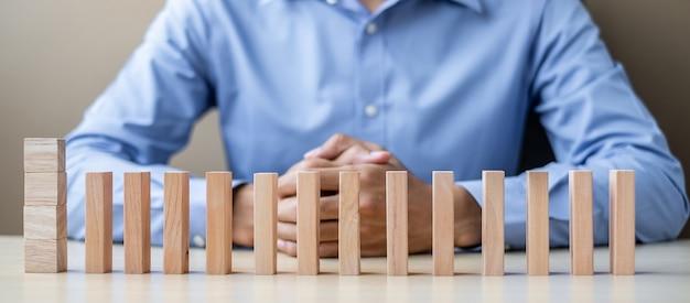 Empresário com blocos de madeira ou dominós. o negócio