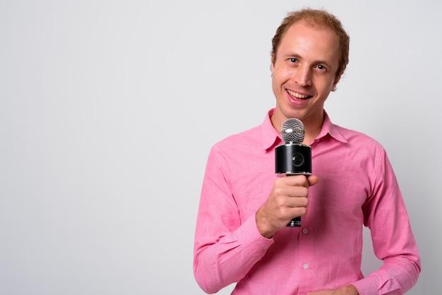 Empresário com cabelo loiro e camisa rosa contra uma parede branca