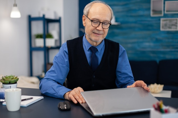 Empresário com cabelos grisalhos abrindo laptop