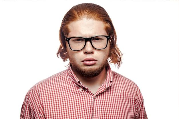 Empresário com camisa vermelha e sardas e óculos olhando para a câmera