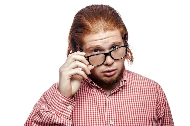 Empresário com camisa vermelha e sardas segurando óculos e olhando para a câmera
