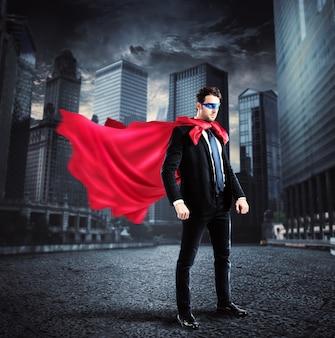 Empresário com capa e máscara de super-herói pousa no asfalto de uma rua da cidade