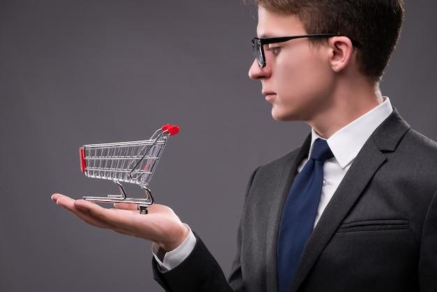 Empresário com carrinho de compras em fundo cinza