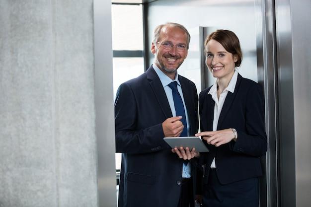 Empresário com colega no elevador