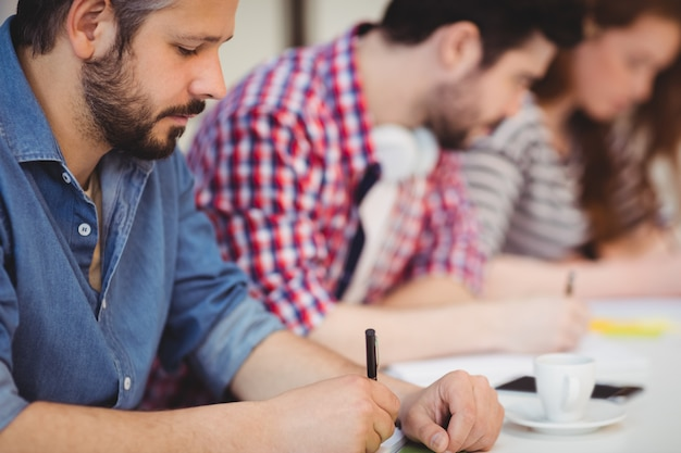 Empresário com colegas de trabalho escrevendo documentos