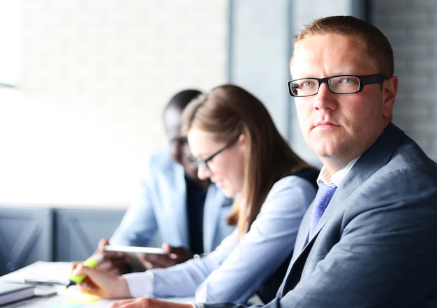 Empresário com colegas em segundo plano no escritório
