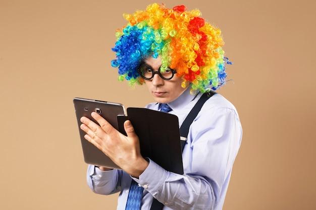 Empresário com computador tablet. retrato de close-up de homem de negócios com peruca de palhaço usando um tablet para acessar a internet. conceito de negócios. multitarefa