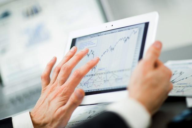Empresário com dedo tocando a tela de um tablet digital